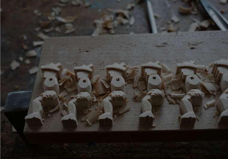 Halb fertige Holzfiguren liegen nebeneinander auf einer Unterlage. Abgehobeltes Holz liegt daneben